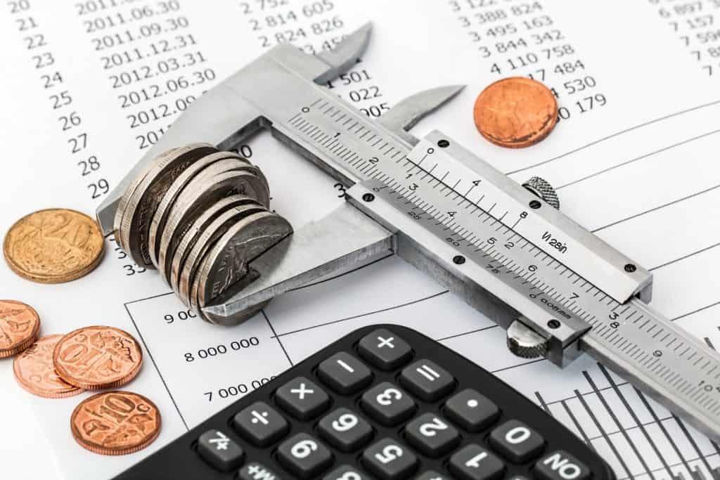 Wydrukowany banknot z leżącym na nim kalkulatorem i monetami