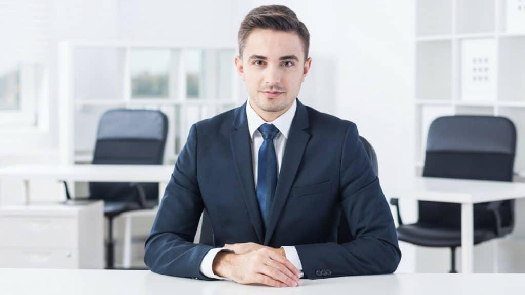 Geschäftsmann im Anzug mit blauer Krawatte am Verhandlungstisch sitzend
