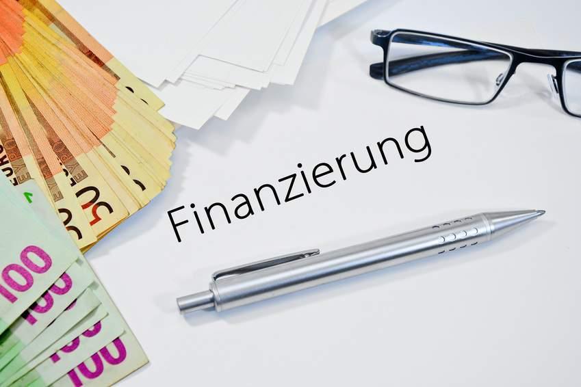 MBI-Finanzierung: Bargeld, eine Brille und ein Kugelschreiber auf dem Verhandlungstisch