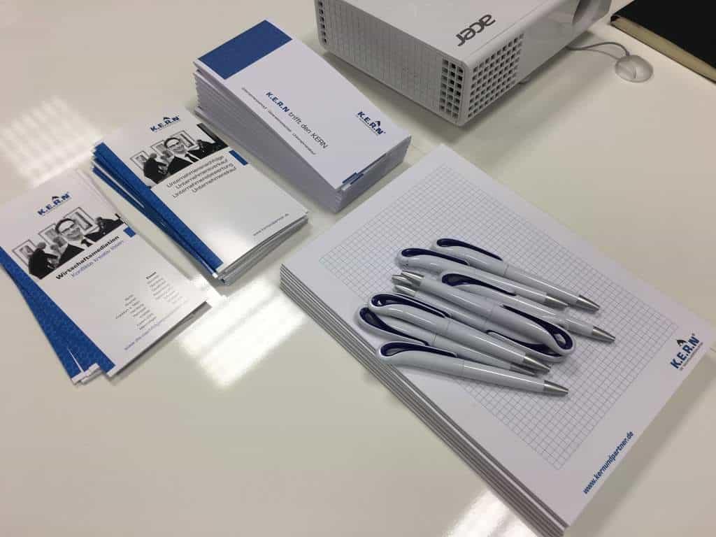 Podkładki, długopisy i broszury KERN z niebieskim logo KERN