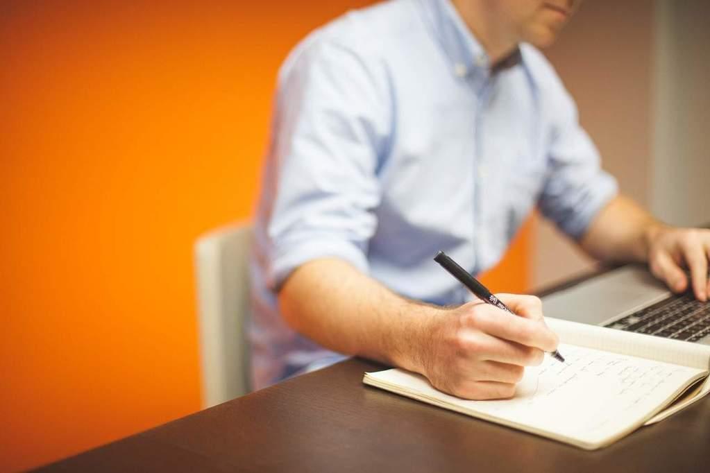 Geschäftsmann schreibt etwas von seinem Laptop in ein Notizbuch ab