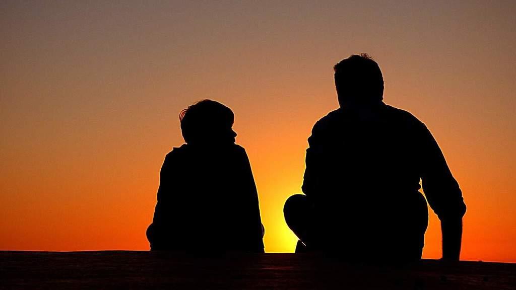 schwarze Silhouette von Vater und Sohn im Sonnenuntergang sitzend