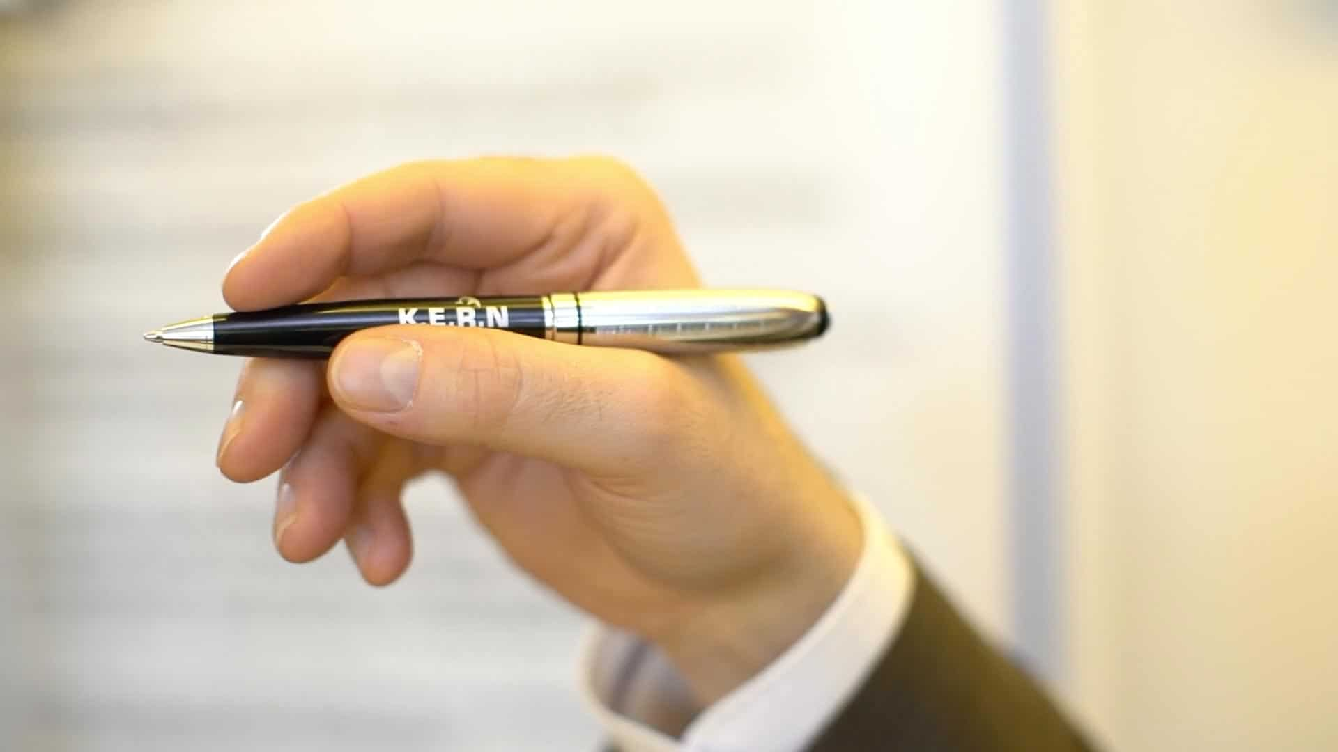 W ręku znajduje się wysokiej jakości pióro KERN w kolorze antracytowym i chromowym