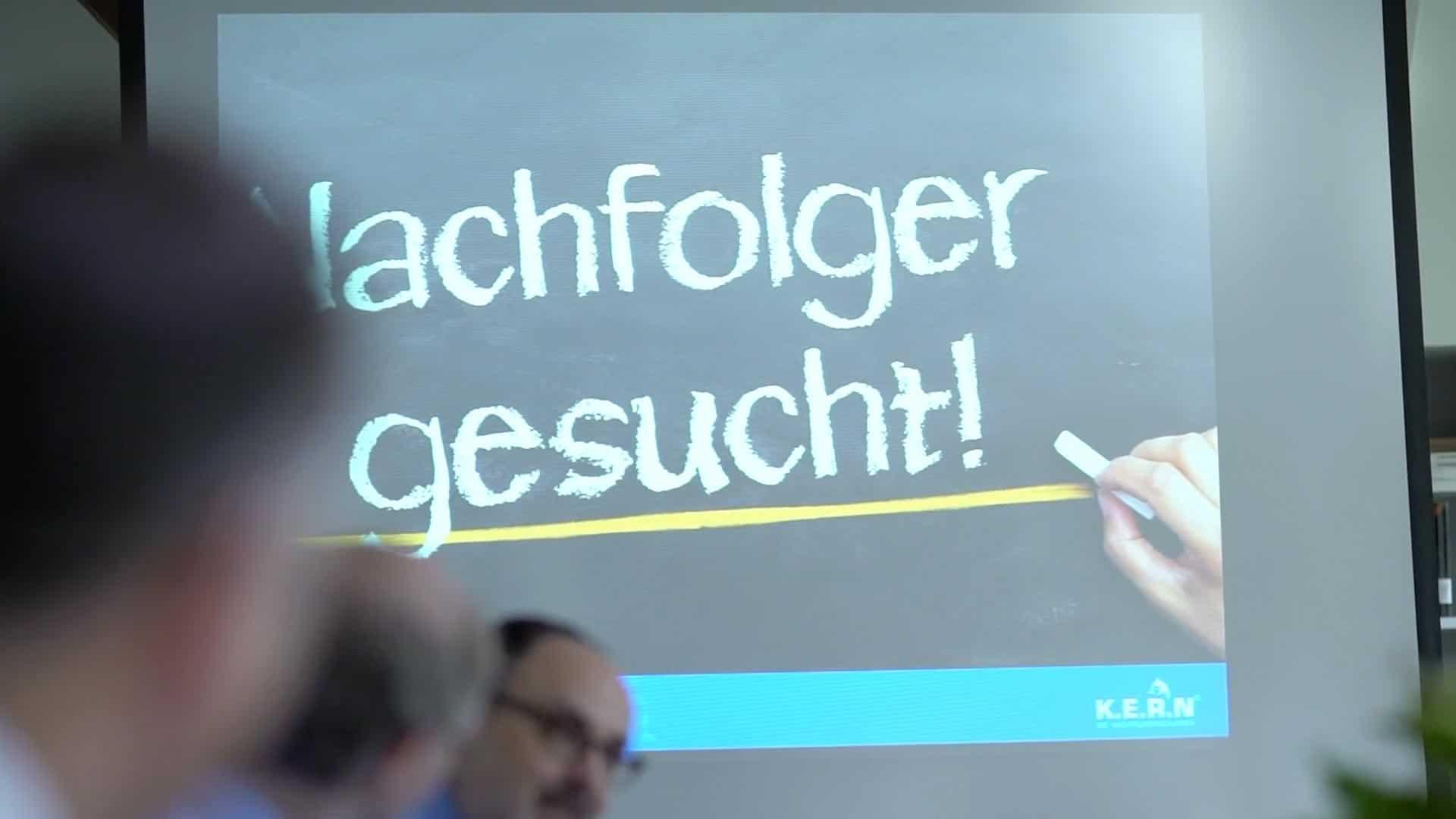 """Specjaliści KERN w sali konferencyjnej, przed ekranem z napisem """"Poszukiwany następca"""