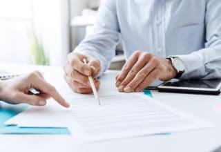 Berater mit einer Kundin bei der Vertragsunterzeichnung