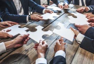 Geschäftsleute an einem Tisch halten Puzzleteile aus weißem Papier zueinander