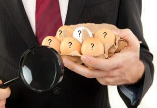 Mann im hält links eine Packung Eier mit Fragezeichen und rechts eine Lupe hoch