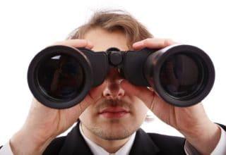 Ein Mann im Anzug schaut durch ein Fernglas