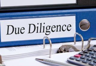 """Bild eines blauen Aktenorders mit der Aufschrift """"Due Diligence"""""""
