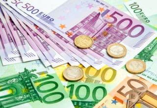 Hundert und Fünfhundert Euroscheine mit Münzen auf einem Tisch