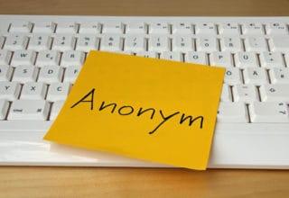 Eine weiße Tastatur mit einem orangenem Klebezettel darauf: Anonym