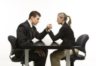 Ein Mann und eine Frau im Anzug veranstalten eine Arm-Drück Wettbewerb