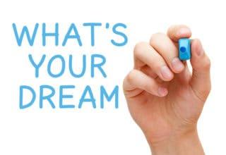 Hand schreibt mit blauem Marker an eine Scheibe: What´s your Dream?