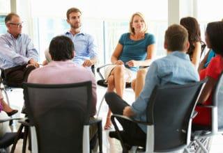 Mitarbeiter sitzen in einem Stuhlkreis zusammen und beraten sich