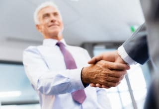 Ein Berater schüttelt einem Kunden die Hand und lächelt dabei