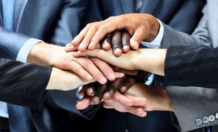 5 Menschen die Ihre Hände in der Mitte übereinander legen und eine Genossenschaft gründen