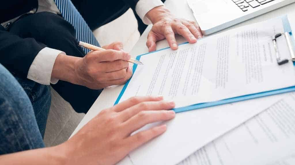 A contract signed by one person. The hand of a second person holds the contract.