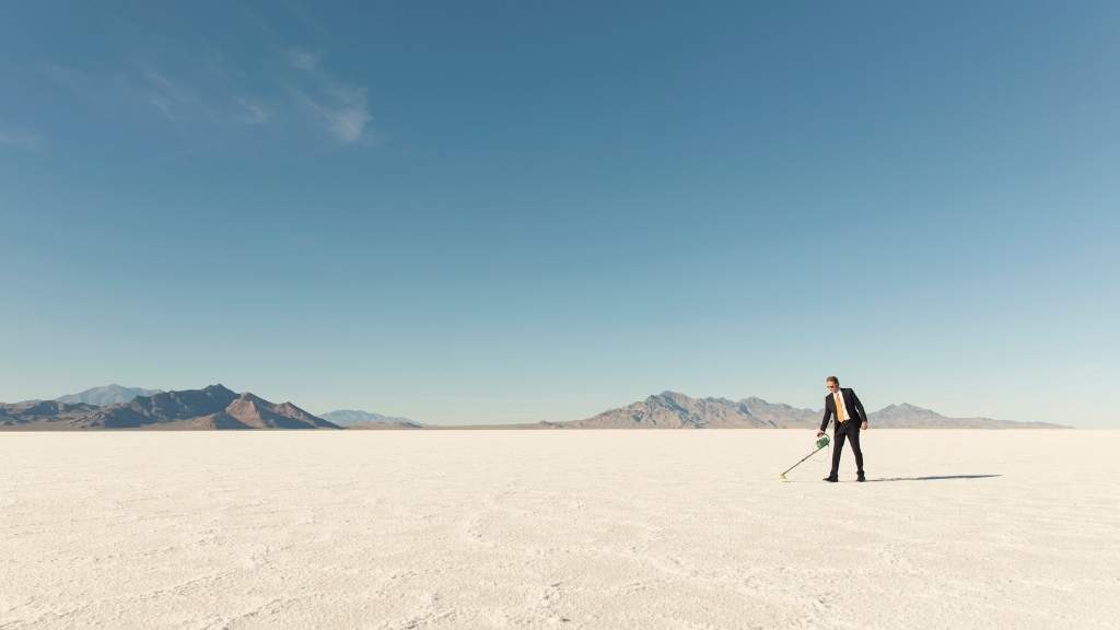 Man in suit searches the ground with a metal detector in a salt desert.