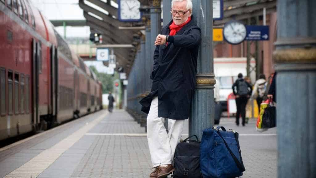 A man stands at the station and looks at his wristwatch.